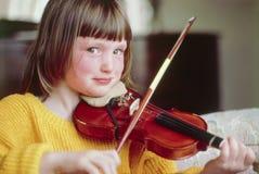 演奏微笑的小提琴年轻人的照相机女孩 免版税库存图片