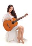 演奏微笑的年轻人的深色的吉他夫人 图库摄影