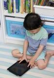 演奏或读研究的泰国儿童男孩片剂在屋子里在bo 库存图片