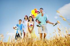 演奏户外儿童领域概念的家庭 免版税图库摄影