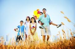 演奏户外儿童领域概念的家庭 库存照片