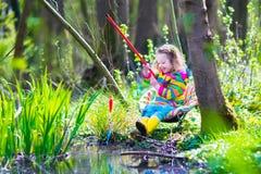演奏户外钓鱼的小女孩 免版税库存图片