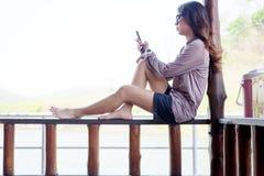 演奏手机的少妇,当坐木阳台时 免版税库存照片