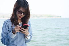 演奏手机的少妇,当站立时和有蓝色se 免版税库存照片