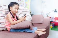 演奏手机的逗人喜爱的亚裔泰国小女孩画象在 免版税库存图片