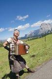 演奏手风琴,真假嗓音陡然互换唱的音乐家在阿尔卑斯 免版税图库摄影