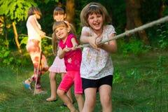 演奏拔河外面在草的小组愉快的孩子 在公园的孩子牵索 免版税库存照片