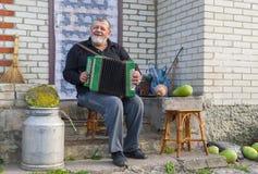 演奏按钮手风琴的乡民 免版税库存图片