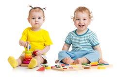 演奏教育玩具的滑稽的孩子被隔绝 库存照片