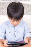 演奏数字式片剂的小男孩 免版税库存图片
