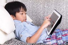 演奏数字式片剂的男孩 免版税库存图片