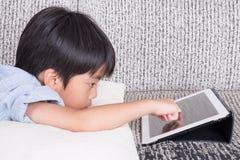 演奏数字式片剂的男孩 免版税库存照片