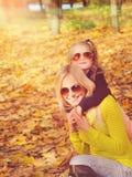 年轻演奏时尚的母亲和小女儿在太阳镜穿戴了在秋天公园 库存图片