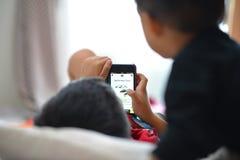 演奏智能手机的孩子 免版税图库摄影