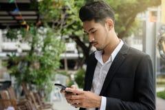 演奏智能手机的聪明的年轻商人 库存图片