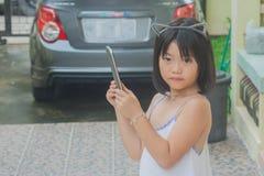 演奏智能手机的逗人喜爱的矮小的亚裔中国女孩 库存图片