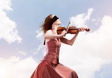 演奏曲调的红色礼服的妇女小提琴手反对多云天空 库存图片