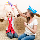 演奏有儿童女孩的美丽的妇女飞机,获得乐趣,愉快微笑的坐沙发 免版税库存照片