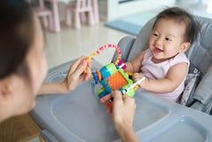 演奏有她的婴孩的亚裔母亲玩具在家坐dinning的椅子 他们是喜欢使用与幸福一起 库存照片