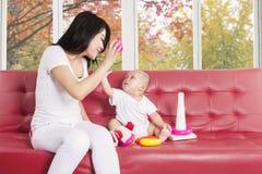 演奏有她的母亲的女婴玩具 免版税库存图片