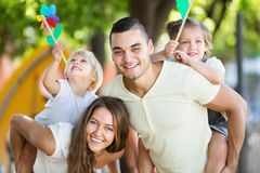 演奏有孩子的年轻家庭五颜六色的风车 免版税库存图片