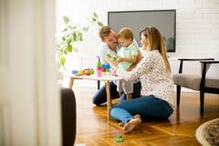 演奏有母亲和父亲的小男孩玩具在现代家 免版税库存照片