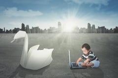 演奏有origami天鹅的男孩膝上型计算机 免版税库存图片