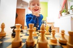 演奏棋认为的小男孩聪明的孩子, 免版税库存图片