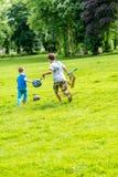 演奏橄榄球夏天的天观点的两个男孩停放 免版税库存照片