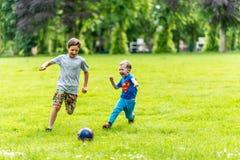 演奏橄榄球夏天的天观点的两个男孩停放 免版税库存图片