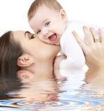 演奏水的婴孩笑的母亲 免版税库存照片