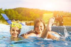 演奏池的子项 两个小女孩获得乐趣在poo 免版税库存照片
