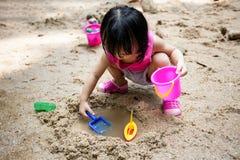 演奏沙子的亚裔中国小女孩在小河 免版税库存照片