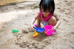 演奏沙子的亚裔中国小女孩在小河 免版税图库摄影