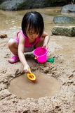演奏沙子的亚裔中国小女孩在小河 图库摄影