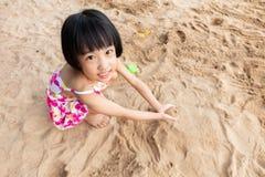 演奏沙子的亚裔中国小女孩在海滩 免版税库存照片