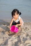 演奏沙子的亚裔中国小女孩在海滩 库存照片