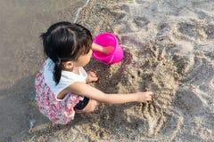 演奏沙子的亚裔中国小女孩在海滩 免版税图库摄影