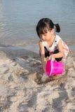 演奏沙子的亚裔中国小女孩在海滩 库存图片