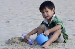 演奏沙子的亚裔男孩 库存图片