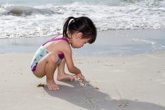演奏沙子的亚裔矮小的中国女孩 免版税库存照片