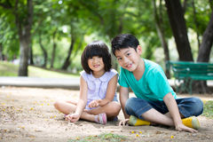 演奏沙子的小亚裔孩子在公园 免版税库存图片