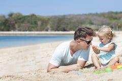 演奏沙子的小女婴戏弄与她的父亲 免版税库存图片