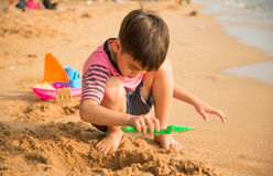 演奏沙子的小男孩在海滩夏天 免版税库存图片