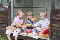 演奏流洒的茶的子项三个年轻人 免版税库存照片