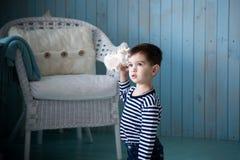 演奏海扇壳的男孩 库存图片