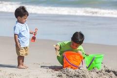 演奏海滩的新西班牙男孩儿童兄弟 免版税库存照片