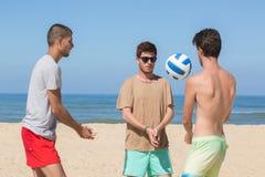 演奏海滩齐射的小组朋友 免版税库存图片