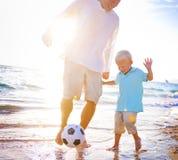 演奏海滩橄榄球幸福概念的父亲儿子 图库摄影