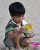 演奏海滩沙子的亚裔男孩 图库摄影